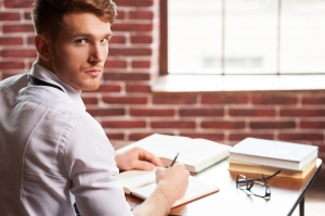 Handsome young man in shirt and tie writing something in note pad and looking over shoulder while sitting at his working place